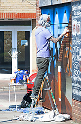 ©Licensed to London News Pictures 27/03/2020  <br /> Bromley, UK. An artist is painting on The Bitter End Bar in Bromley, South East London. While the country is in lockdown this artist is making the most of the empty streets by creating a mural of people enjoying a drink at a bar. The Prime Minister Boris Johnson has asked people to stay at home to help in the fight against Covid-19 and to only go out for essential reasons. credit:Grant Falvey/LNP