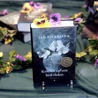 """Nederland,Den Haag,11 december 2005..Schrijver Jan Siebelink is te gast voor een interview in boekhandel Paagman en signeert  zijn laatste roman """"Knielen op een bed violen"""".Roman.Literatuur.Etalage.Violen."""