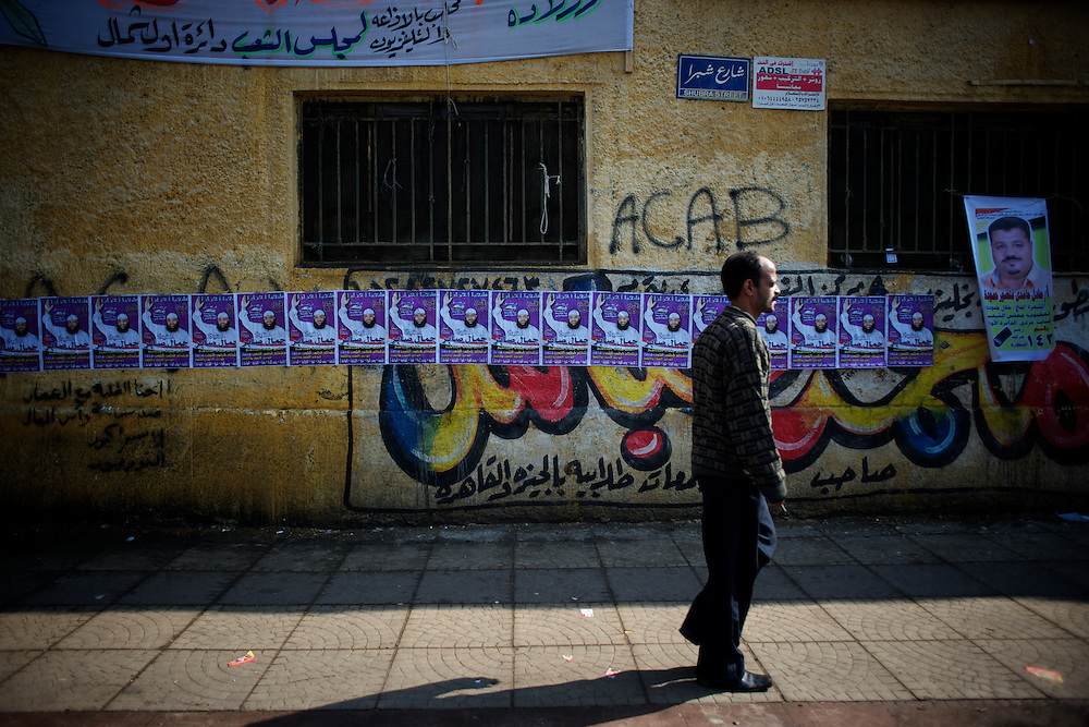 A man passes by campign poster in Cairo's Shubra district.