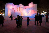 Three Japanese children pose for the camera in front of a giant ice sculpture of eagles and owls at the 2009 Sapporo Snow Festival, held in Odori Park