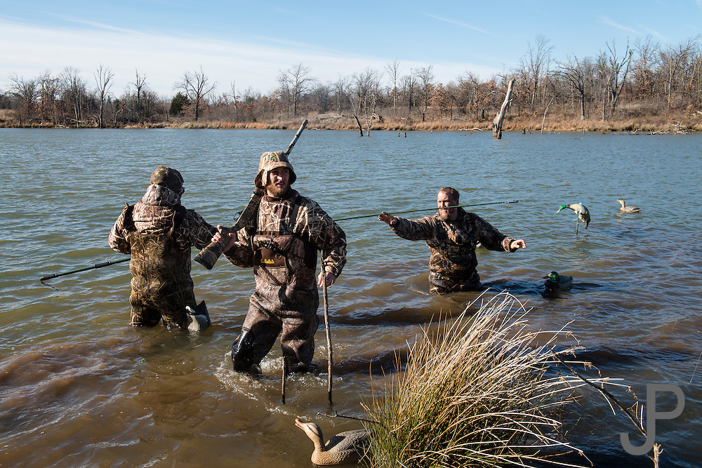 Hunters reposition decoys while duck hunting in Shamrock, Oklahoma
