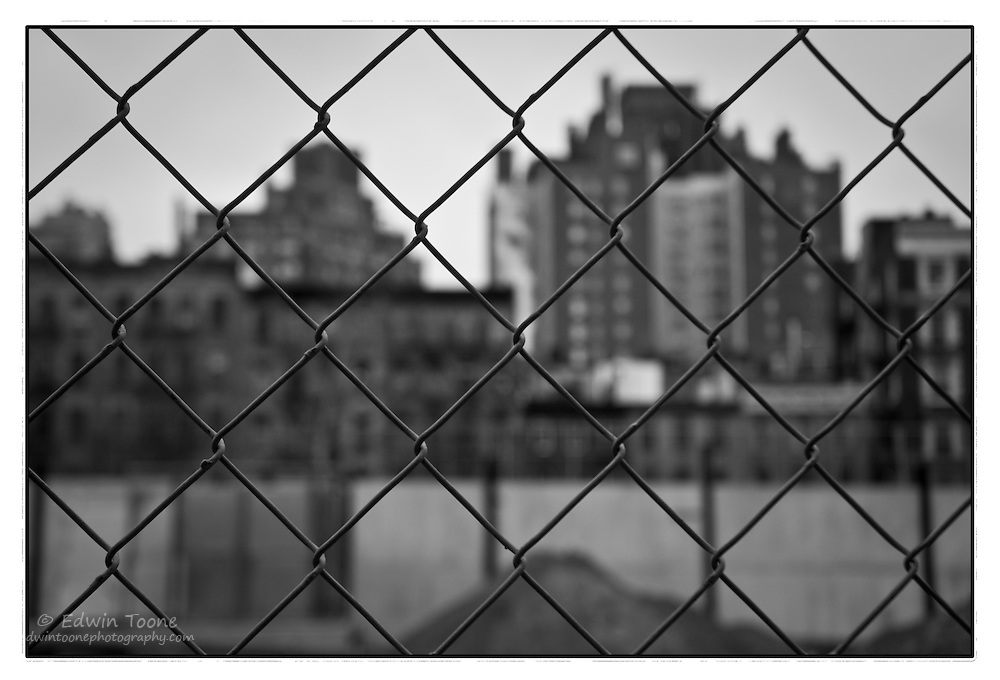 Close up of a fence with city buildings in the background.