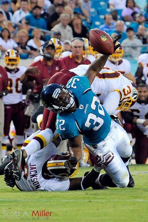 Sept. 3, 2009; Jacksonville, FL, USA; Jacksonville Jaguars running back Maurice Jones-Drew (32) fumbles the ball as he is hit by Washington Redskins defensive end Rob Jackson (91) and safety LaRon Landry (30) during their game at Jacksonville Municipal Stadium. ©2009 Scott A. Miller