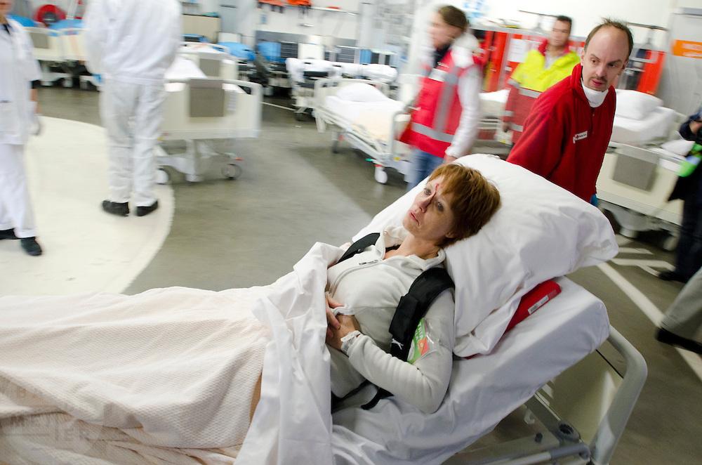 Een slachtoffer wordt op een ziekenhuisbed van de ambulancesluis naar het ziekenhuis vervoerd.  In het Calamiteitenhospitaal in Utrecht wordt een rampenoefening gehouden. De nadruk ligt op de contaminatie, door een gekantelde vrachtwagen zijn veel slachtoffers in aanraking gekomen met een chemische stof. Voor het eerst wordt er geoefend met een zogenaamde decontaminatietent. Als de tent bevalt, schaft het ziekenhuis zo'n tent aan. Bij de 'ramp' zijn 100 slachtoffers gevallen.<br /> <br /> A victim is brought in to the hospital. In the Trauma and Emergency Hospital in Utrecht an calamity training was held. The emphasis is on the contamination by an overturned truck, many victims are contaminated by a chemical. For the first time a so-called decontamination tent was used. If the tent fulfills the expectations, a tent will be purchased. The 'calamity' caused 100 victims.
