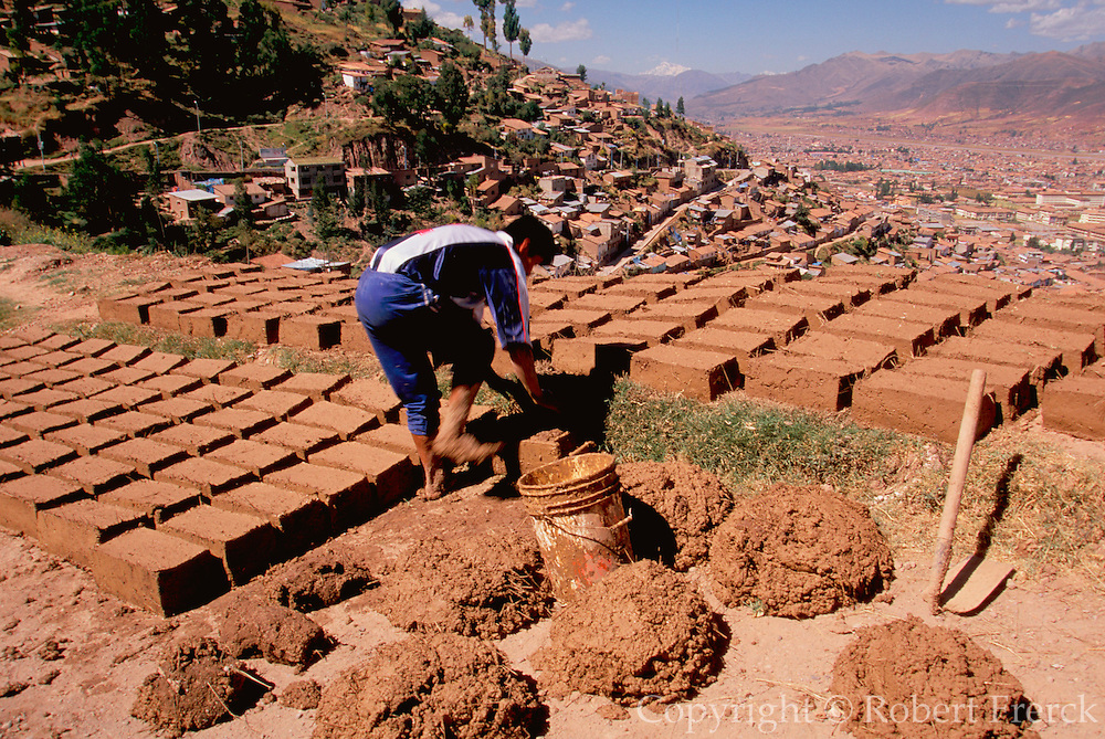 PERU, HIGHLANDS, CUZCO worker building with adobe bricks