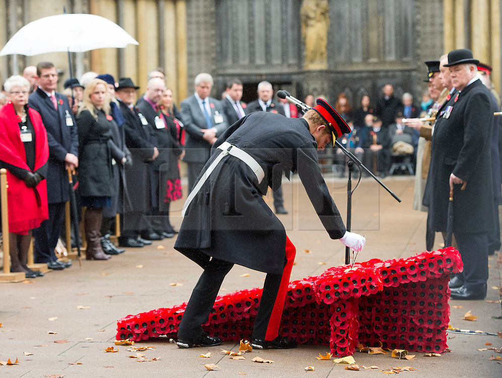 © Licensed to London News Pictures. 04/11/2015. London, UK. PRINCE HARRY laying a cross during the service. A Service to mark the opening of the Filed of Remembrance at Westminster Abbey, attended by Prince Philip, Duke of Edinburgh and Prince Harry.  The Field of remembrance is a memorial garden to commemorate British and Commonwealth military and civilian servicemen and women in the two World Wars and later conflicts. Photo credit: Ben Cawthra/LNP