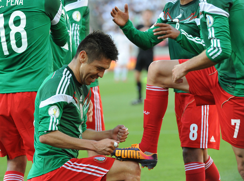 Mexico's Oribe Peralta polishes the team mates Miguel Layun boots after scoring against New Zealand  in the World Cup Football qualifier, Westpac Stadium, Wellington, New Zealand, Wednesday, November 20, 2013. Credit:SNPA / Ross Setford