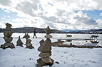 Justice Daniels, walks his dogs, Merlin and Baloo, during an outing Thursday along the shoreline of Lake Coeur d'Alene near North Idaho College where a number of rocks stacks have been constructed on the beach.