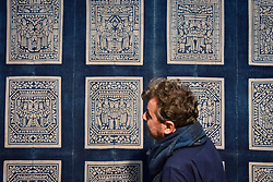 © Licensed to London News Pictures. 03/10/2017. London, UK. A visitor views a Chinese indigo marriage panel from the early 20th century at the Decorative Antiques & Textiles Fair taking place at Evolution in Battersea Park which runs 3-8 October 2017 and features more than 160 exhibitors. Photo credit : Stephen Chung/LNP