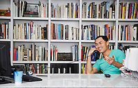 Mid adult man using phone in front of bookshelf