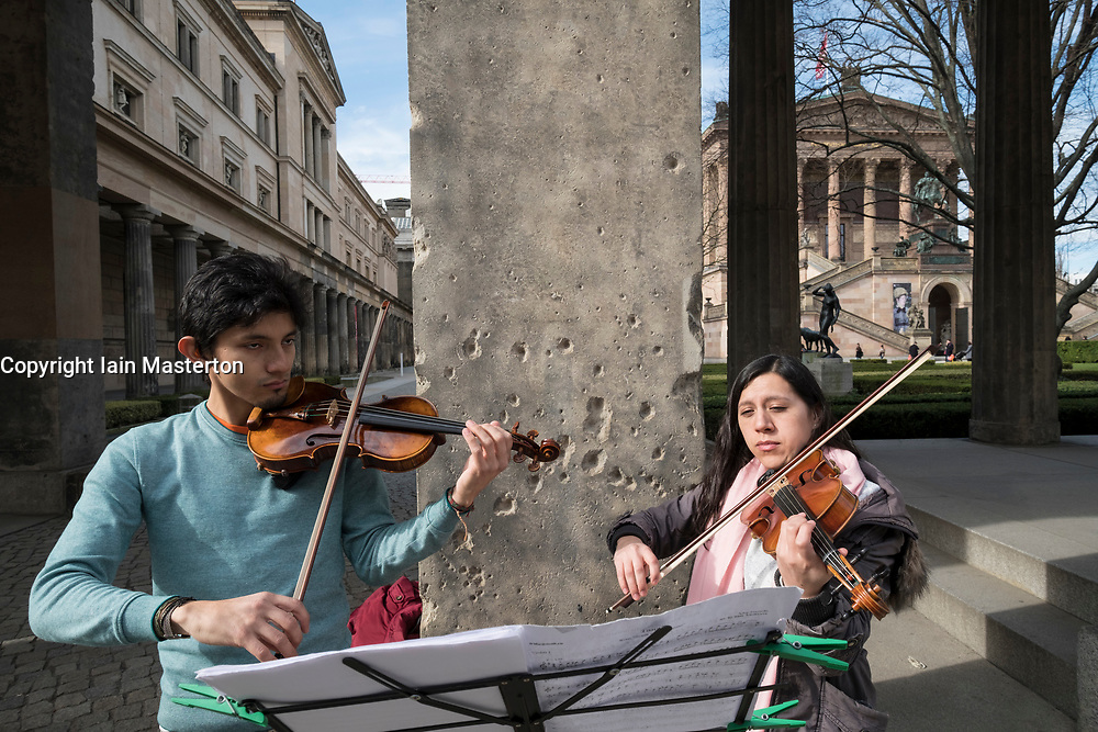 Buskers playing outside Neues Museum with WWII bullet holes in column behind, Berlin, Germany.