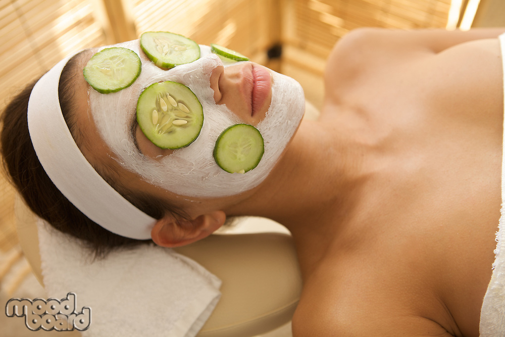 Young woman lying down on massage table with cucumbers on eyes and face