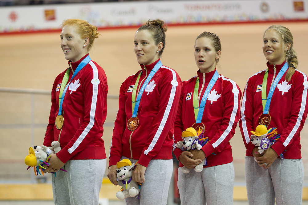 The Canadian gold medal winning team of (L-R) Allison Beveridge, Laura Brown, Jasmin Glaesser and Kirsti Kay listen to the national anthem during the medal ceremony for the women's cycling team pursuit at the 2015 Pan American Games in Toronto, Canada, July 17,  2015.  AFP PHOTO/GEOFF ROBINS
