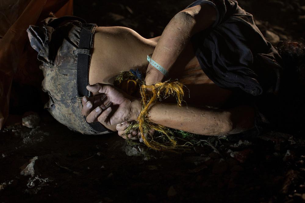 San Pedro Sula, Honduras<br /> <br /> En yngre man har dumpats mitt p&aring; grusv&auml;gen. Hans h&auml;nder &auml;r h&aring;rt bakbundna och hans kropp full med kulh&aring;l. <br /> <br /> Photo: Niclas Hammarstr&ouml;m