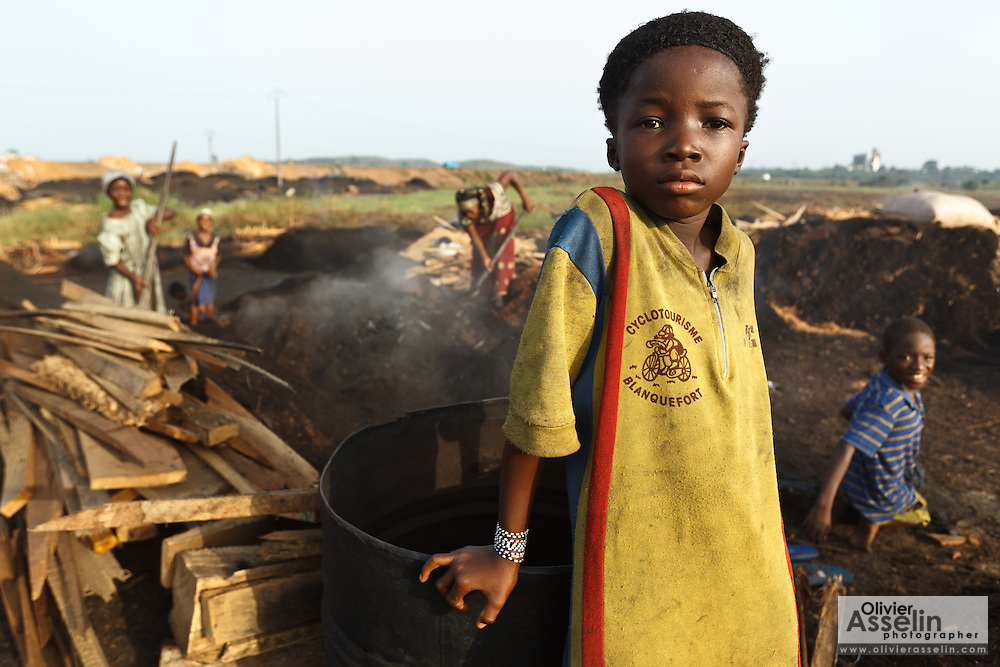 A girl rests against a metal barrel at a wood charcoal production site on the outskirts of San Pedro, Bas-Sassandra region, Côte d'Ivoire on Sunday March 4, 2012. Men, women and children - who don't go to school - work here seven days a week.