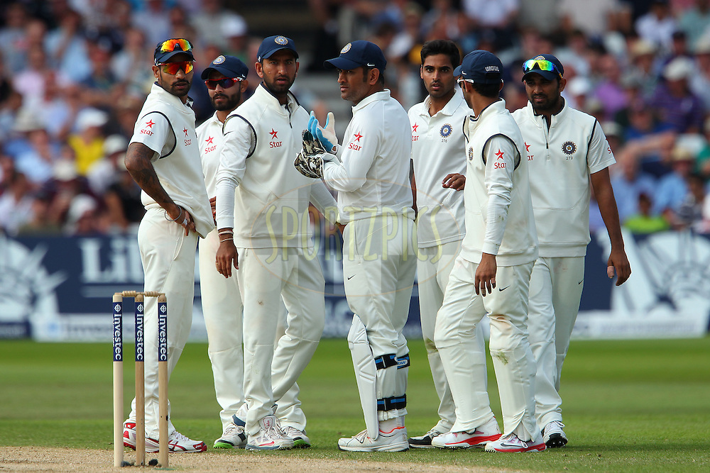 Mahendra Singh Dhoni captain of India and team mates look on as Stuart Broad of England departs  during day three of the first Investec test match between England and India held at Trent Bridge cricket ground in Nottingham, England on the 11th July 2014<br /> <br /> Photo by Ron Gaunt / SPORTZPICS/ BCCI