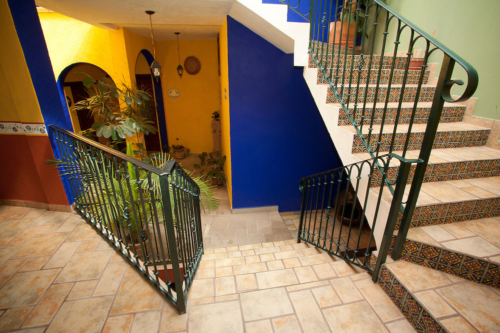 North America, Mexico, Guanajuato State, Guanajuato, arches and stairs of hotel courtyard wtih plants and Mexican tiles.  The historic city of Guanajuato is a UNESCO World Heritage Site.  PR