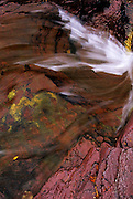 Closeup of Ptarmigan Falls and red rock Grinnell Formation in fall. Ptarmigan Creek in Glacier National Park, Montana