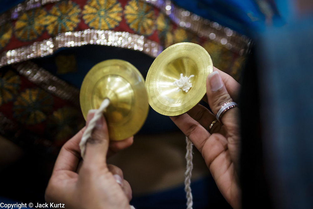 10 AUGUST 2012 - PHOENIX, AZ:  A woman holds small cymbals during the celebration of Janmashtami at Ekta Mandir, a Hindu temple in central Phoenix. Janmashtami is the Hindu holy day that celebrates the birth of Lord Krishna. Hindu communities around the world celebrate the holy day. In Arizona, most of the Hindu temples in the Phoenix area have special celebrations of the day.  .PHOTO BY JACK KURTZ