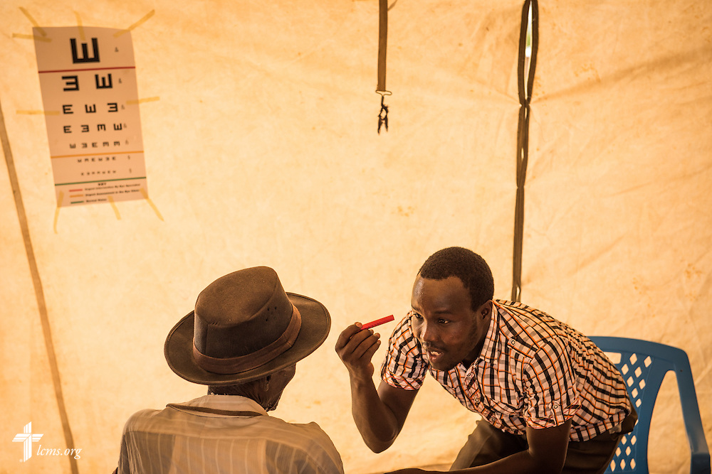 A Kenyan health worker examines a patient's eyes at the  LCMS Mercy Medical Team on Monday, June 20, 2016, in Nataparkakono, a village in Turkana, Kenya.  LCMS Communications/Erik M. Lunsford