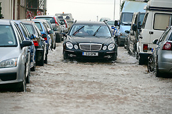 © Licensed to London News Pictures. 03/02/2014. Exmouth, UK. Cars are surrounded by the water. Seawater floods the seafront in Exmouth Devon.The water breached defences and flooded Morton Road, St Andrews Roads, Victoria Road and some of the other surrounding streets. Police closed the road to vehicles. Officials were seen delivering sandbags to the local residents. . Photo credit : Russ Nolan/LNP