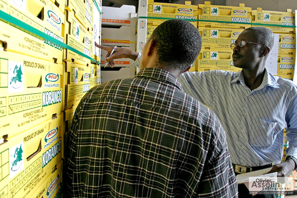 Men looking at pineapple crates in warehouse