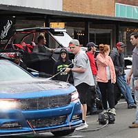 Tanner Palmer sprays down a car ahead of a show car display Saturday evening.