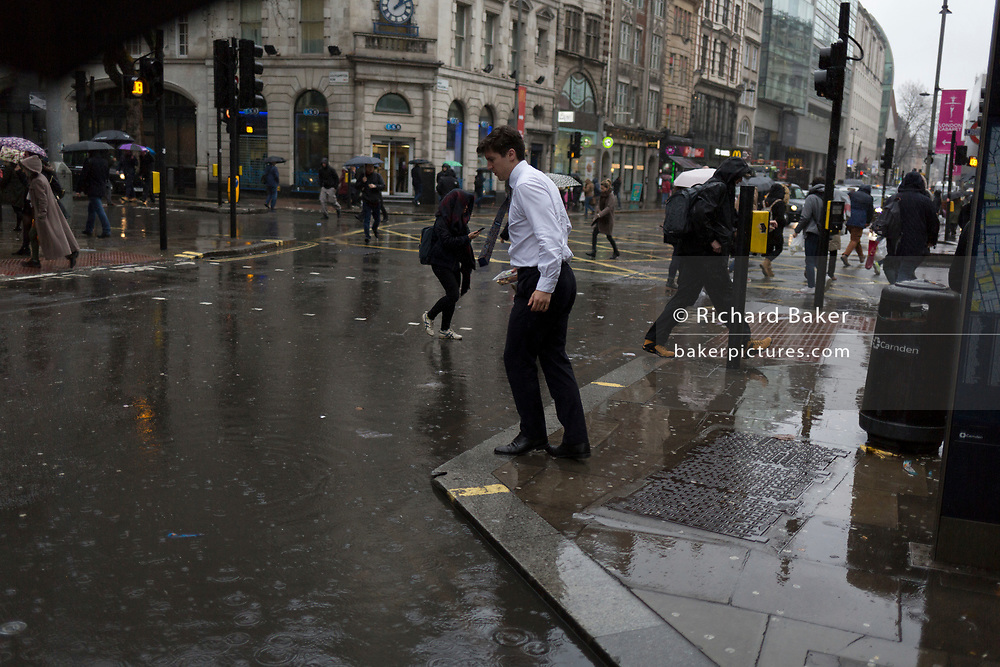 Storm Georgina swept across parts of Britain and in central London, lunchtime office workers were caught out by torrential rain and high winds, on 24th January 2018, in London, England. Pedestrians resorted to leaping across deep puddles at the junction of New Oxford Street and Kingsway at Holborn, the result of overflowing drains. First in a sequence of five photos.