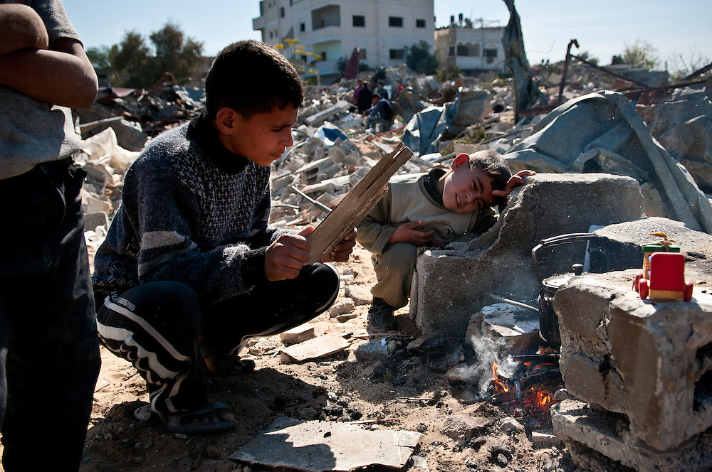 Boys build a small fire to make tea near the wreckage of their family home in Beit Lahia, in the northern Gaza Strip, which was destroyed Operation Cast Lead