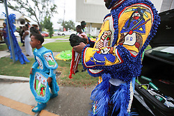 29 August 2014. Lower 9th Ward, New Orleans, Louisiana. <br /> Survivors of the storm. Mardi Gras Indian Michael 'Spy Boy' Tenner (10 yrs) of the Comanche Hunters and Robert 'Flag Boy Slim' Stevenson of the Hard Head Hunters get ready to lead a touching second line parade along Tennessee Street in the Lower 9th Ward in memory of those who perished in the storm 9 years ago. <br /> Photo; Charlie Varley/varleypix.com
