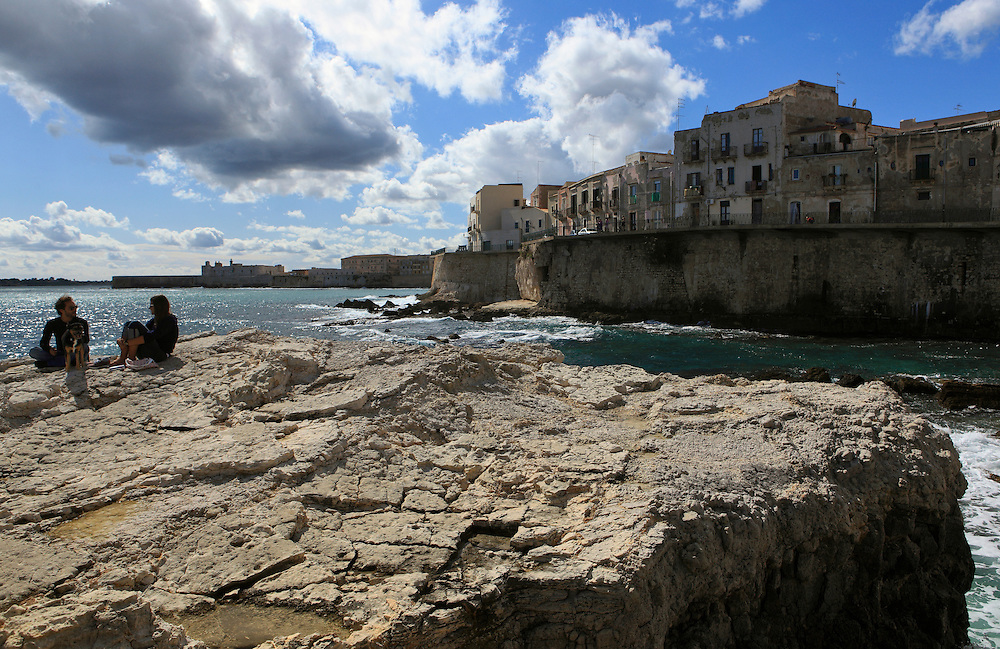 Couple enjoying the sun on a rock near the city's seawall in Syracuse, Sicily. Syracuse is famous for its rich Greek history, culture, amphitheaters, architecture, and as the birthplace of Archimedes. This 2,700 year-old city played a key role in ancient times, when it was one of the top powers of the Mediterranean world.