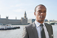 Portrait of an African American businessman standing in front of river