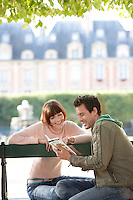 Young couple reading guide book sitting on bench in park