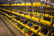 "Individual trays for airline baggage in the Early Bags Store where 4,000 pieces are held. 50-70,000 pieces of British Airways baggage a day travel through 11 miles of conveyor belts which were installed in a 5-storey underground hall beneath the 400m (a quarter of a mile) length of Terminal 5 at Heathrow Airport. Here we see items of luggage spending 4 hours in transit, held in a fully-automated parking lot for bags. Computers decide when to fish the item out and re-introduce it into the system and load it on to the appropriate aircraft. T5 alone has the capacity to serve around 30 million passengers a year and was completed in 2008 at a cost of £4.3bn. The system was designed by an integrated team from the airport operator BAA, BA and Vanderlande Industries of the Netherlands, and handles both intra-terminal and inter-terminal luggage. From writer Alain de Botton's book project ""A Week at the Airport: A Heathrow Diary"" (2009)."