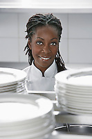 Female chef near stacked plates in kitchen portrait