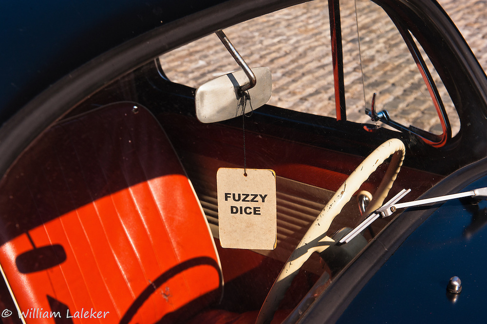"""Fuzzy Dice"" hangs from a car mirror, appearing in concept and context only as a form of Metaphysical Kitsch."