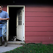 Caption 8<br /> John McCloud heads out of his house to do some evening chores:  feeding the animals and performing artificial inseminations on his sows, September 24, 2013.