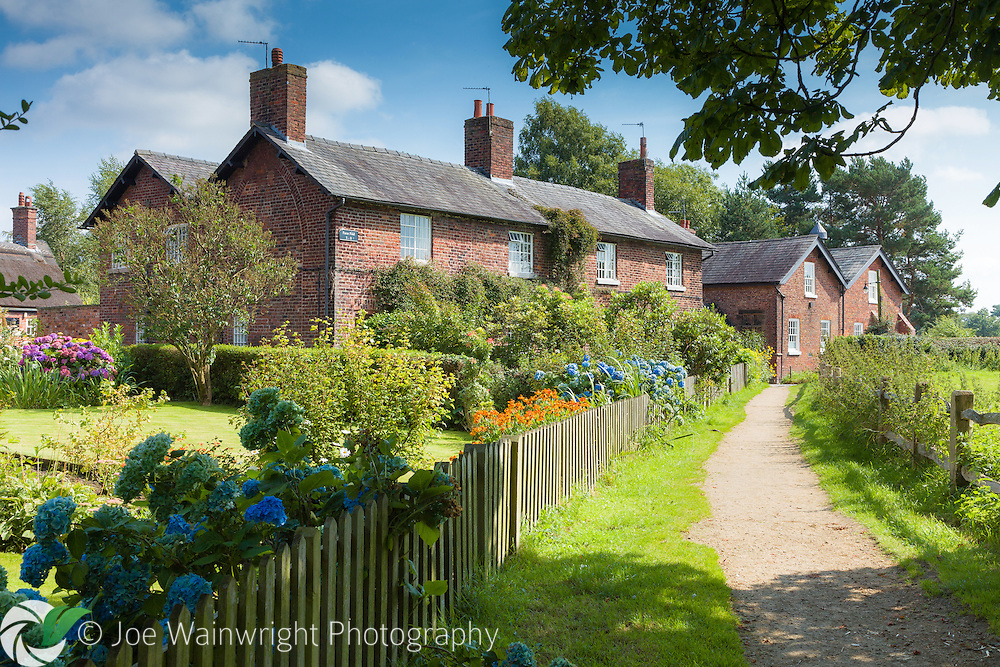 Pretty gardens complement the terraced cottages at Styal, Cheshire.