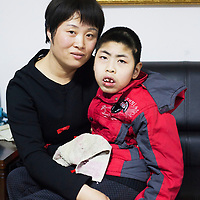 Beijing, March 11 : Tian Peng, 15, is taken care of by his mother Cui Xinying while his little brother Tian Ye, 3, plays in the apartment.<br />
