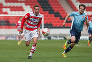 Doncaster Rovers Midfielder Matty Blair (17) in action Blackpool Defender Andy Taylor (Captain) (3) gives chase during the EFL Sky Bet League 2 match between Doncaster Rovers and Blackpool at the Keepmoat Stadium, Doncaster, England on 17 April 2017. Photo by Craig Zadoroznyj.