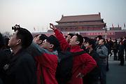 13 Mars 2012 vers 18h25, 8&deg;C. Alors que les deux assembl&eacute;es terminent leurs travaux dans le Palais du peuple, sur le cot&eacute; ouest de la place Tiananmen, des badauds se pressent pour assister &agrave; la descente des couleurs pour la nuit avec la Cit&eacute; interdite en arri&egrave;re plan. Les deux photographes  en rouge et noir effectuent probablement un tour des sites &quot;rouges&quot; de la r&eacute;volution chinoise, devenu un parcours populaire dans le pays. Les couleurs rappellent celles des r&eacute;volutionnaires chinois.<br /> <br /> ---------------------------------<br /> ENG:<br /> 13 March 2012, around 18h25, 8&deg;C.<br /> Dozens of onlookers are gathered at Tiananmen Square to see the national flag ceremony organized everyday at sunrise and sunset.  On the other side of the square, the Two Assemblies are finishing their annual sessions. In the background the balcony where Mao Zedong has declared the foundation of the RPC in 1949.