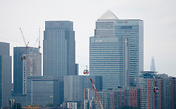 © Licensed to London News Pictures. 28/06/2012. LONDON, UK. With Canary Wharf in the background, Emirates Air-Line cabins are seen in action over East London today (28/06/12) at the launch of London's first cable car system. The new cable car system, running across the River Thames between the Greenwich Peninsula and the Royal Docks in East London, was today opened to the public, despite fears that it would not be ready in time for the London 2012 Olympics. Photo credit: Matt Cetti-Roberts/LNP