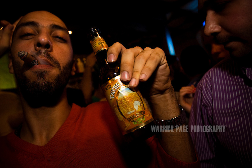 RAMALLAH, WEST BANK - JUNE 24: A Palestinian man holds a bottle of Palestinian-made Taybeh beer in the Orjuwan Lounge, on June 24, 2010, in Ramallah, West Bank. Nightlife in Ramallah is on the rise as numerous restaurants and bars are opening throughout the de facto capital of the West Bank, as economic growth has been steady since 2007 in spite of the ongoing occupation. NGO workers, international travellers and the youth of Palestine's elite, are flocking to the city's cosmopolitan scene, in-part due to the growth of venues, but also due to the restrictions on movement enforced by the Israeli occupation limiting options. (Photo by Warrick Page)