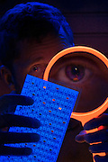 Man used a magnifier to inspect the back side of a ballot for hanging chads.Black light