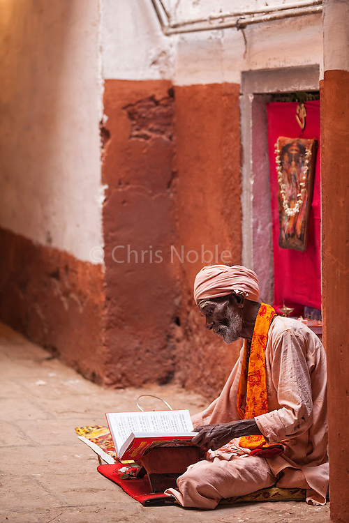 Portait of a holy man reading in one of the galis (alleyways) near the Ganges River in the old section of the holy city of Varanasi, India.