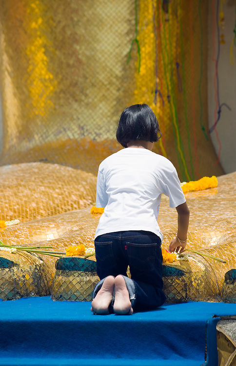 Girl laying an offering of flowers at the Giant Buddha Wat Intharawihan Bangkok Thailand.&amp;#xA;<br />