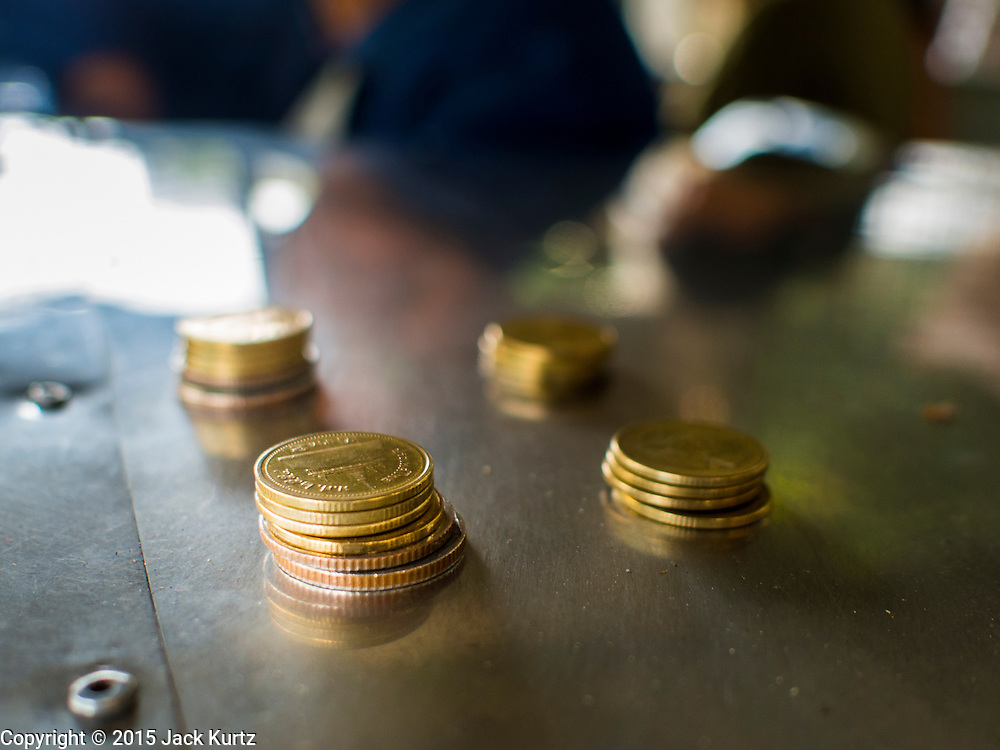 19 JANUARY 2015 - BANGKOK, THAILAND: Coins in the fare collector's booth of the Khlong Saen Saeb on the Sukhumvit Road side of Khlong Saen Saeb. The small ferry crosses Khlong Saen Saeb throughout the day. It is powered by an diesel engine that uses a system of cables to pull the ferry the 30 feet across the canal. It's used by pedestrians  who need to get across the khlong. The nearest bridge is about ½ mile away.     PHOTO BY JACK KURTZ