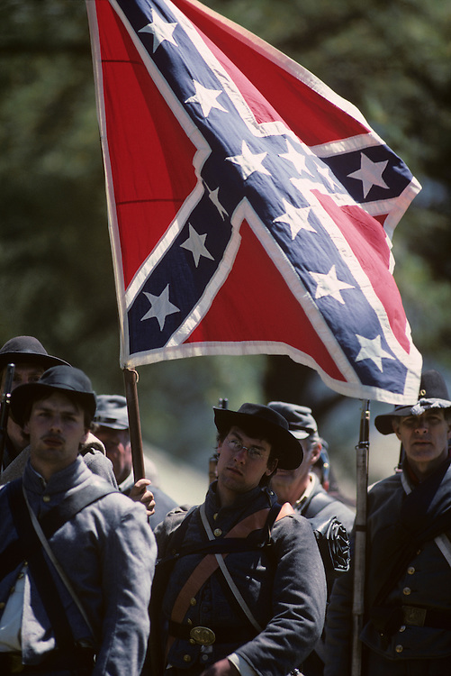 USA, Virginia, Confederate soldier carries battle flag during reenactment of Civil War Battle of Chancellorsville
