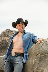 muscular cowboy with an open shirt outdoors against rocks