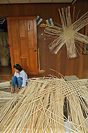 Thai woman working with material for weaving baskets, near Chiang Rai, Thailand